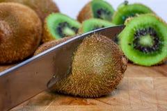 Horizontal shot of knife cutting kiwi fruits royalty free stock images