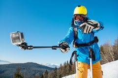 Male skier using selfie stick taking photos while skiing. Horizontal shot of a male skier having fun outdoors taking a selfie with action camera on a monopod Stock Photos