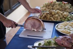 Male chef hand with knife slicing a crispy roasted pork joint. Horizontal shot of open kitchen with chef cutting meat on a white board positioned on a table with Stock Image