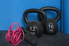 Two cast-iron kettlebells, of 12 and 16 kg, and skipping rope. Horizontal shot of pile of sport equipment used for muscle toning, aerobic and weight training Royalty Free Stock Image