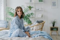 Horizontal shot of pretty woman sits in lotus pose on bed, dressed in casual outfit, listens pleasant melody in earphones, sits ag. Ainst cozy interior. People royalty free stock images