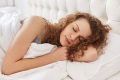 Horizontal shot of pretty young woman sleeps sweetly at bed, see royalty free stock image