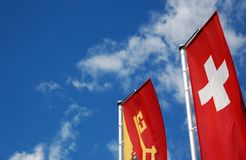 Swiss and Geneva canton flags in sunny sky stock photo