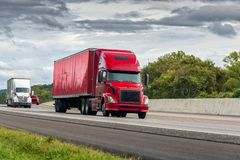 Red Semi Tractor-Trailer Travels The Interstate Highway. Horizontal shot of a red semi tractor-trailer truck traveling the interstate highway stock image