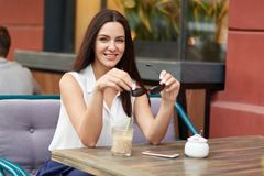 Horizontal shot of relaxed beautiful European woman holds shades, wears white blouse, has long hair, drinks cocktail, poses in out stock photography
