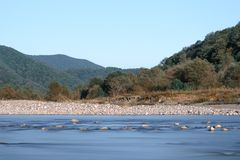 Horizontal shot of the river in the valley on the background of mountains and blue sky. Royalty Free Stock Photography
