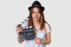 Horizontal shot of shocked beautiful young female film producer holds movie clapboard, wears hat, casual white t shirt, has stupef stock photos
