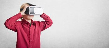 Horizontal shot of small boy wears VR glasses, sees virtual reality, isolated over white background with copy space for advertisin Stock Photos