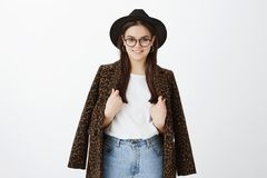 Horizontal shot of stylish feminine fashion blogger in trendy hat, glasses and coat with leopard print over t-shirt. Touching clothes and smiling broadly while stock photography