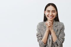 Horizontal shot of stylish happy european girlfriend in jacket, clasping hands together over chest and smiling joyfully. Being glad receiving great awesome royalty free stock images