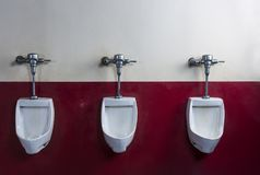 Horizontal shot of three urinals on a red and white wall Stock Photography