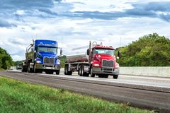 Two Gasoline Tanker Trucks on the Interstate. Horizontal shot of two gasoline tanker trucks on the interstate. One has a red cab and the other a blue cab. Cloudy stock photo