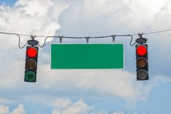 Red Traffic Light With Blank Street Sign. Horizontal shot of two red traffic lights hanging from a cable with a blank street sign in-between with blue sky and Royalty Free Stock Photo