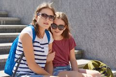 Horizontal shot of two sisters embrace and pose at camera, wears trendy sunglasses, stroll outside, carry rucksacks, feel glad. Street style and friendship royalty free stock image
