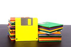 Old Floppy Disks With Blank Yellow Disk Front. Horizontal shot of two stacks of old plastic disks with a yellow disk standing up against one stack.  Front side Royalty Free Stock Photo