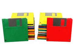 Two Stacks of Floppy Disks With Two Standing Front. Horizontal shot of two stacks of old plastic multicolored disks.  A green disk is leaning against one stack Stock Photos