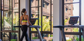 Horizontal shot of woman jogging on treadmill at health sport club at luxury resort. Female working out at a gym running Stock Images