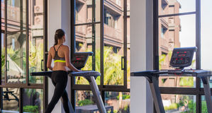 Horizontal shot of woman jogging on treadmill at health sport club at luxury resort. Female working out at a gym running. On a treadmill with a great summer Royalty Free Stock Photos