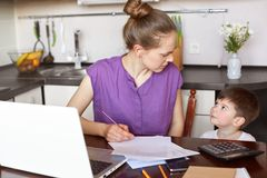 Horizontal shot of working mum being busy with documentation, makes financial report or calculates family budget, surrounded with. Papers and laptop, looks at stock photography