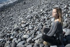 Young blonde Caucasian female sitting in a relaxing, meditating position with eyes closed, wearing a neutral outfit on the beach. Horizontal shot of young blonde Royalty Free Stock Photos