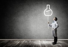 Doctor and vial symbol. Horizontal shot of young confident doctor in white medical uniform interracting with glowing vial symbol whie standing against dark gray stock photos