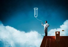 Doctor and vial symbol. Horizontal shot of young confident doctor in white medical uniform interracting with glowing vial symbol whie standing on brick roof with stock images