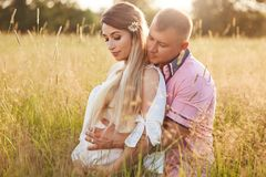 Horizontal shot of young family embrace and keep hands on tummy, anticipate for child, pose in green field, have walk during sunny. Day. Pregnant female spends stock image
