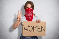 Horizontal shot of young female expresses womens protest, holds plait with inscription Women, makes peace sign, wears red bandana. On face, isolated over stock photography