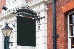 Square empty signboard on a building with classical architecture. Horizontal side view of empty black square signage on a British building with classical Royalty Free Stock Photography