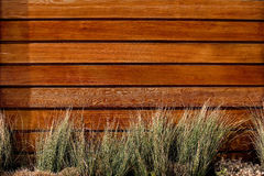 Horizontal slat wood fence. With bunches of grass Royalty Free Stock Image