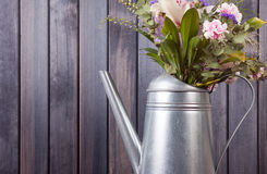 Horizontal still life flowers in watering in grunge can dark wooden background Royalty Free Stock Image