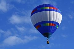 Horizontal Strips Hot Air Balloon. A beautiful horizontally striped hot air balloon floats in a blue sky Royalty Free Stock Images