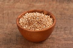 Sorghum raw seeds. Horizontal studio shoot of sorghum seeds bowl on wooden background stock image