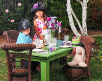 Horizontal Tea Party in the Garden. Horizontal format of Six year old girl playing tea party with her three year old brother in the garden Stock Images