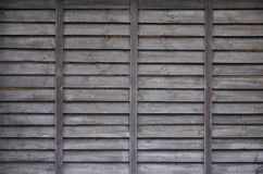 Horizontal texture of a wall from several rows of brown old wooden boards. Painted wooden wall in brown colo. R royalty free stock photography