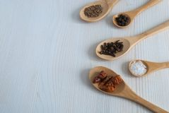 Horizontal top view of five wooden spoons with spices royalty free stock image