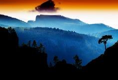 Horizontal vdramatic mountain trees on rocks silhouette sunset b Royalty Free Stock Photos