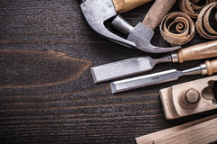 Horizontal version of planer hammer metal chisels. Wooden studs and curled shavings on vintage wood board construction concept Royalty Free Stock Photography