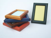 Horizontal and vertical picture frames. Four  coloured , blue, orange, mahogany,teak picture frames stacked horizontally on top of each other and one green Stock Images