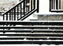 Vertical and horizontal lines on buildings provide interesting contrast in this snowy scene. Horizontal and vertical railings offer sharp contrast as black stock photo