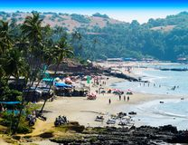 Horizontal vibrant Indian beach with crowd of people background. Dense goa cafe bar relax crowdy vivid bright color rich blue sky tidal waves composition design stock images