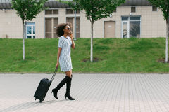 Horizontal view of the cheerful afro-american girl holding the luggage while talking via the mobile phone. Royalty Free Stock Images