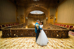 The horizontal view of the cheerful dancing newlywed couple in the old castle. Stock Photography