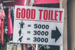 A horizontal view of classic simple design handmade wooden sign of toilet give direction to WC. Bali. Indonesia royalty free stock photography