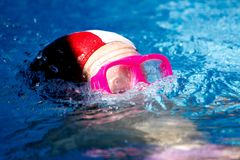 Horizontal View of Close Up of Little Girl Who Dives into the Po. Ol with a Pink Diving Mask Royalty Free Stock Images