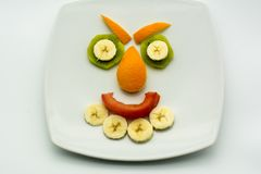 Horizontal View of Close Up some Pieces of Fruit Forming a Face. Expression with Banana, Kiwi, Orange and Tomato stock photos