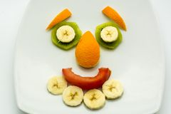 Horizontal View of Close Up some Pieces of Fruit Forming a Face. Expression with Banana, Kiwi, Orange and Tomato royalty free stock photos