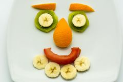 Horizontal View of Close Up some Pieces of Fruit Forming a Face. Expression with Banana, Kiwi, Orange and Tomato royalty free stock image