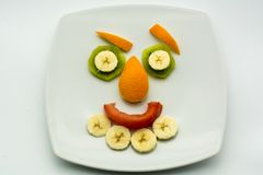 Horizontal View of Close Up some Pieces of Fruit Forming a Face. Expression with Banana, Kiwi, Orange and Tomato royalty free stock photography