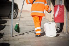 Horizontal View of a Dustman Cleaning the Street With a Mop Wear Stock Photos